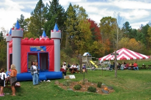 Outside view the bounce house and picnic tent set up with guests all around